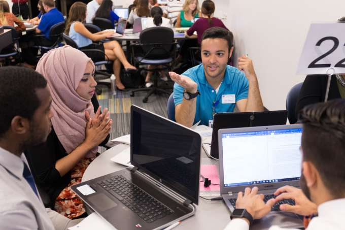 small group of students discussing a class topics around a laptop computers.