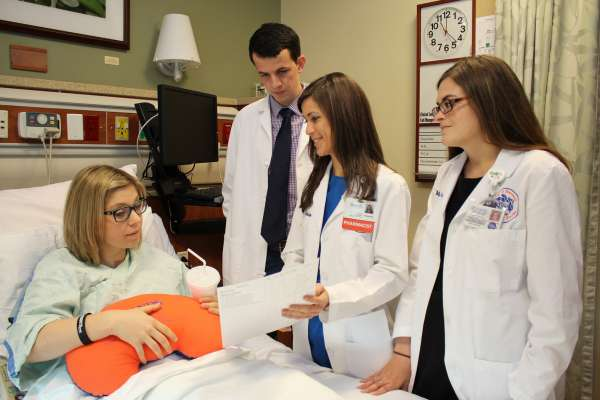 health professional students gathered around a patient in a hospital bed sharing health information to the patient.